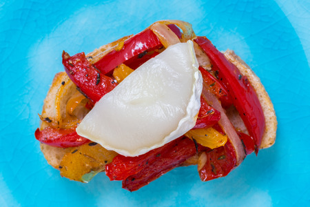 Bruschetta with peppers and goats cheese on a turquoise plate. Stock Photo