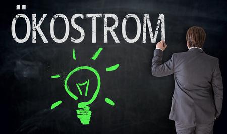 electricity providers: Businessman writes Ökostrom (in german eco power) on blackboard concept. Stock Photo