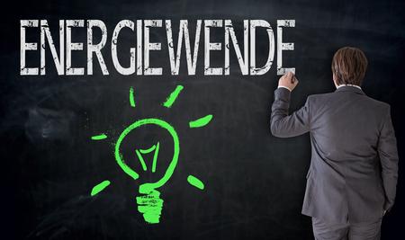 energy suppliers: Businessman writes  Energiewende  (in german energy revolution) on blackboard concept. Stock Photo
