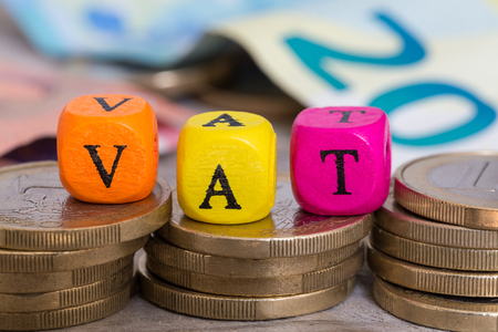 VAT letter cubes on coins concept. Stock Photo