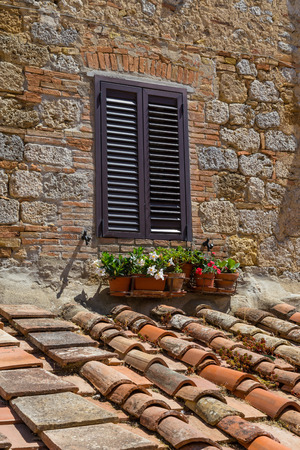 Window with shutter in Tuscany with flowers and brick.