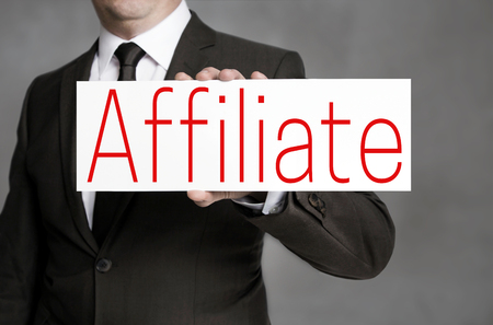 Affiliate signboard is held by businessman.