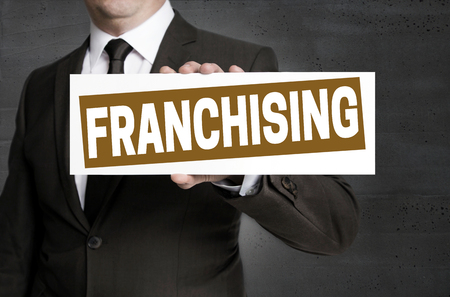 Franchising sign is held by businessman.