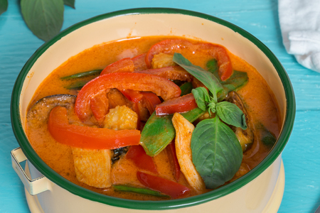 Red Thai curry in a bowl on turquoise wooden table.