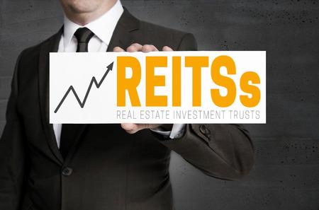 REITs sign is held by businessman concept. Reklamní fotografie