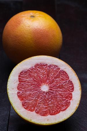 Grapefruit sliced on mahogany wood background.