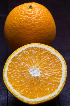 caoba: Naranja en rodajas sobre fondo de madera de caoba.