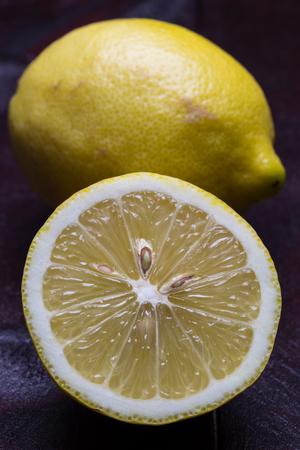 Lemon cut open on mahogany wooden background.