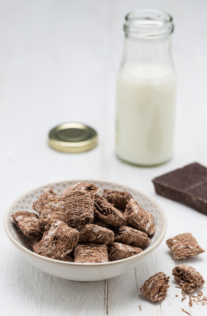 Chocolate wheat flakes in a bowl and milk bottle. Stock Photo