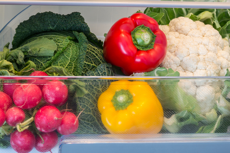 Open fridge filled with fruits and vegetables.