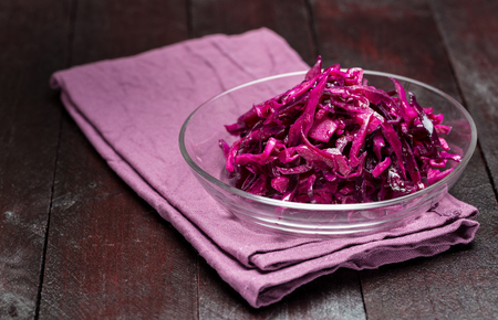 Red cabbage salad in a glass bowl and wooden background. Stock Photo