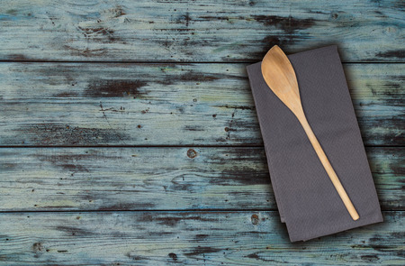 Wooden spoon and kitchen towel on turquoise vintage wood.