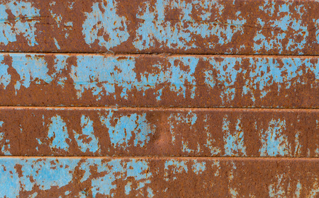 Blue paint rests on rusty structure.