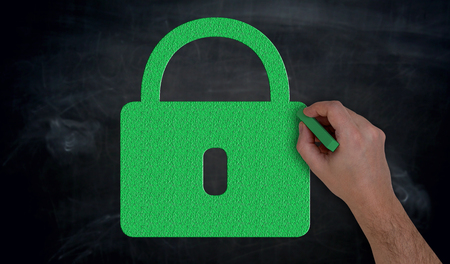 Hand paints with chalk green U-lock on blackboard concept. Stock Photo