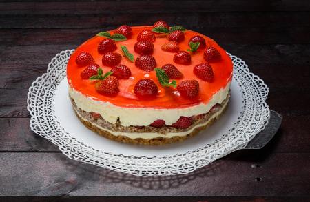 Strawberry cream cheese cake on mahogany wood background.