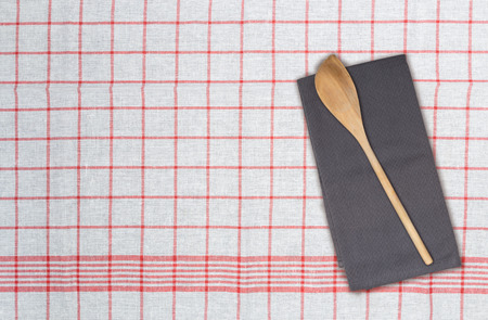 Wooden spoon and kitchen towel concept.