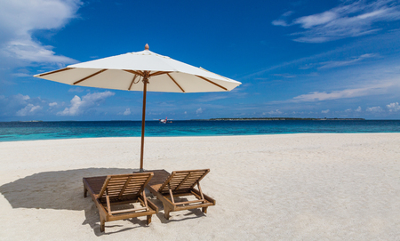 Parasol and sunbeds on the beach Atoll island Maldives.