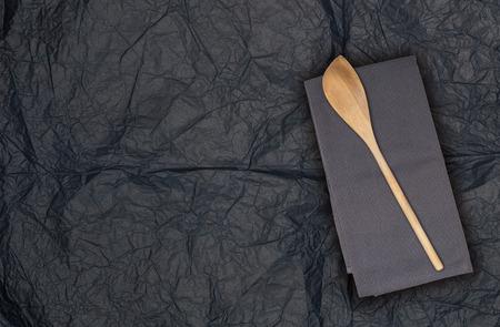 Cuchara de madera y paño de cocina sobre papel de seda.