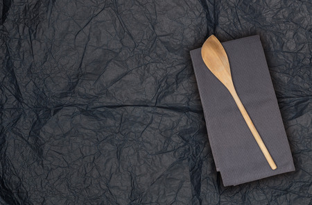 Wooden spoon and kitchen towel on tissue paper.