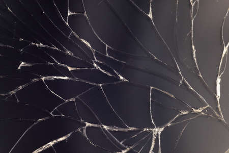 Close-up macro of broken dark glass. Abstract black background with white lines. Elements of smartphone (screen).