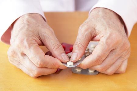 Elderly woman holding pills