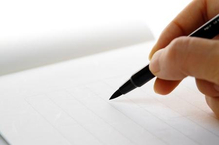 hand holding a fudepen (calligraphy pen)                                  Banco de Imagens