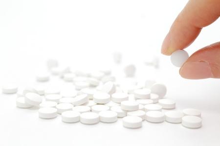 painkiller: Female hand holding pill Stock Photo