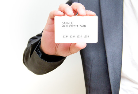 non cash: businessman in black costume and orange necktie reach out on camera and show credit card or visiting card, close up