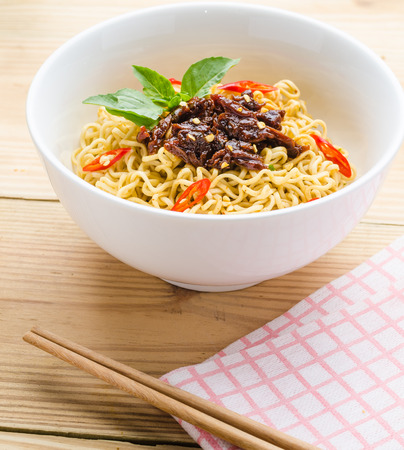 Instant noodles in white black on wood background