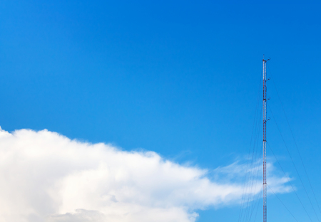 atmospheric: mast in blue sky with white soft cloud