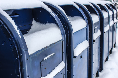 Snow on Row of Blue Mail Boxes Stock Photo