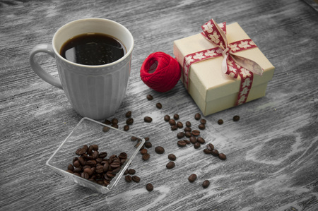 hank of threads, gift box, coffee beans and cup of cofee on gray