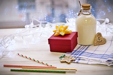 A bottle of cream and a gift on the table