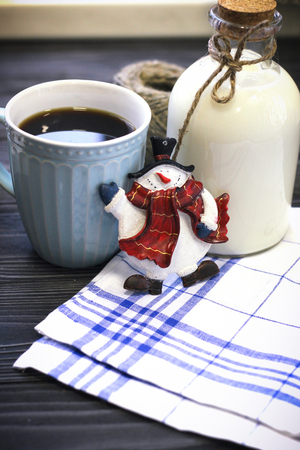 Festive still life with a bottle of milk, a cup of freshly brewed fragrant coffee, a hank of threads, a checkered tablecloth on a gray wooden table, a dark background Stock Photo