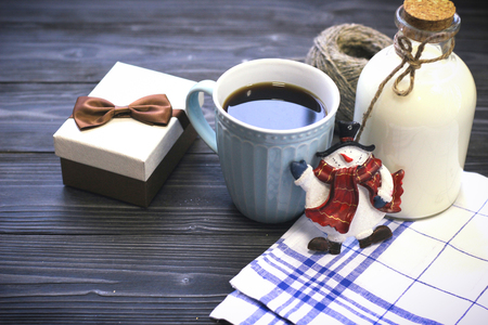 Festive still life with a bottle, a cup , a box, a snowman Stock Photo