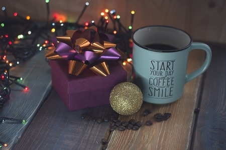 Gift box and cup of coffee, gold inscription on the table