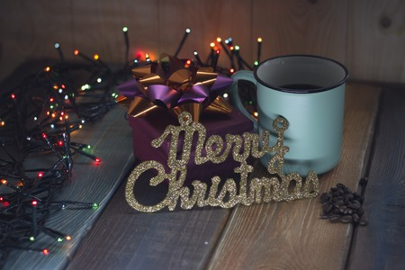 Gift, the inscription Marry Christmas and cup on the table