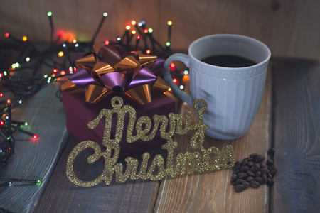 The inscription Marry Christmas and cup of coffee on the table