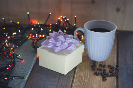 White gift box, blue cup, coffee beans on the table