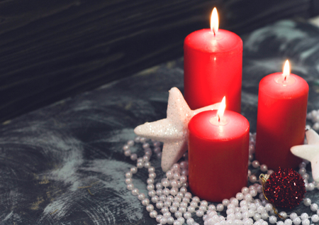 Red burning candles with white christmas decorations Stock Photo