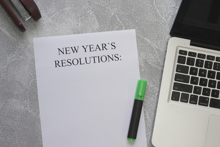 New Years resolutions paper, a green highlighter, a laptop and a stapler on a lifgt concrete background, top view
