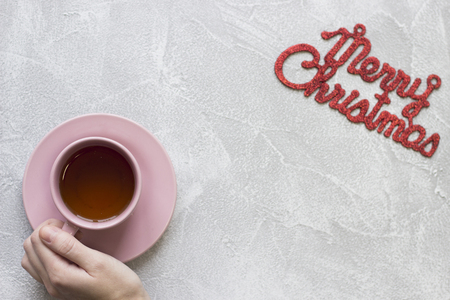 Pink tea cup with saucer and Merry Christmas inscription Stock Photo