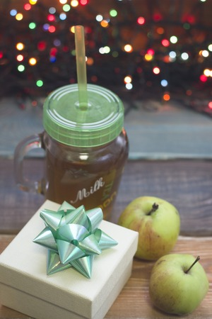 A festive still life with a white giftbox, glass cup of tea with a cap, green apples, fairy lights