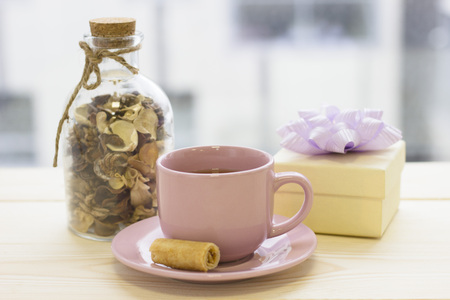 A bright morning with a cup of tea, a gift box and a bottle with dry flowers