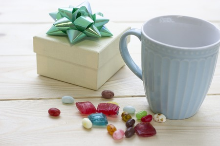 Christmas still life with a light blue blue porcelian mug and a beige gift box with a green metalic bow. Colored candies spilled on a light wooden table. Close up