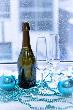 Two glasses, a bottle of champagne and Cristmas-tree decorations Stock Photo
