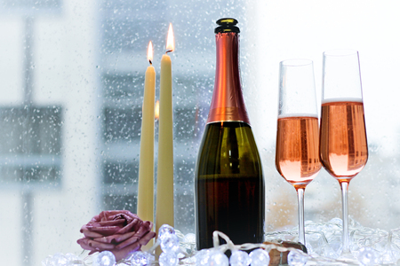 A festive morning for a couple. Two filled glasses and a bottle of rose sparkling wine with two burning candles. A lilac rose and white fairy lights on a white wooden table. Rainy day. Light background