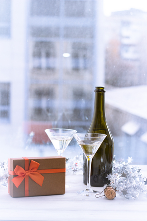 Still life with a bottle of champagne, two glasses and a gift box