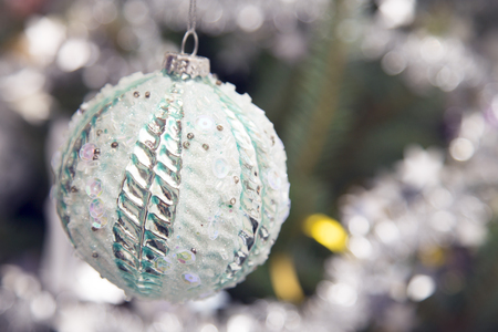 An unusual white Christmas bauble with sequins and beads hanging on a Christmas tree. Blurred background. Close up Stock Photo