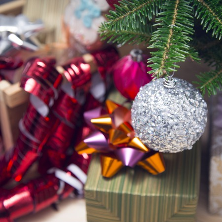 Gifts under a decorated Christmas tree. A green striped gift box with a purple-orange metallic bow.A selective focus on a silver glitter ball. Close up. Colorful blurred background Stock Photo